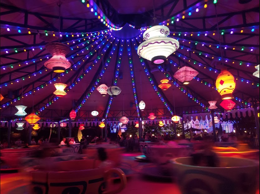 Photo of the Mad Hatter teacup ride at Hong Kong Disneyland. It is night and there are lanterns and lights hanging from the tent-like structure covering the ride. There are large teacups blurred because they are in motion. The teacups have people inside.