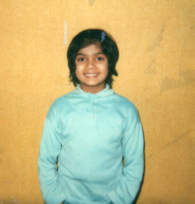 A picture of Nisha, age 6 or 7. She is standing against a yellow backgrop. She has a light blue pullover. Her hair is black and chin-length and she has a matching barette in her hair.