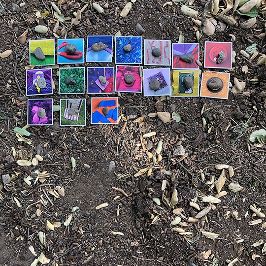 A still photo of seventeen Rainbow Squared cards laid out in a grid under an oak tree amidst California hills.