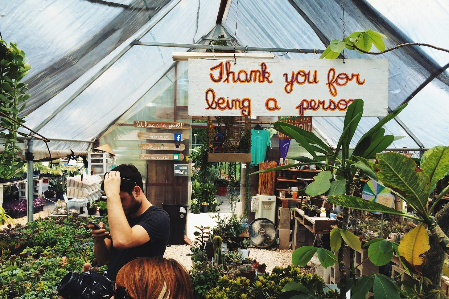 Two people shopping in a plant store, a sign hangs over them that reads Thank You For Being a Person.