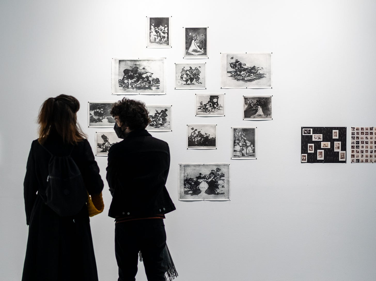 Gallery view of intaglio prints on the wall. Two people stand and chat in front of the prints, masks on.