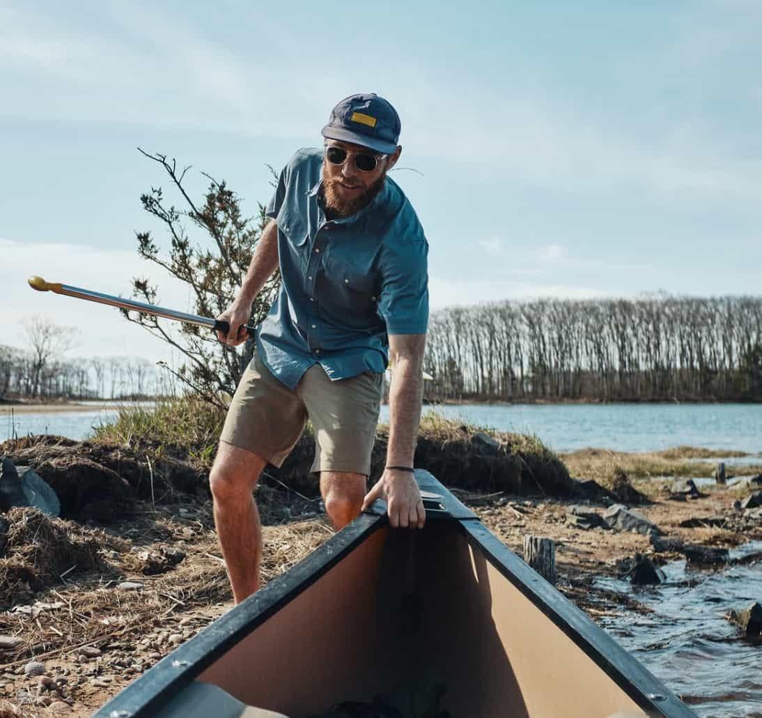 man wearing wellen eddy shirt pushes a canoe into a lake