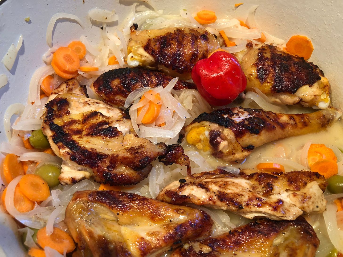 Grilled chicken pieces simmering in a dutch oven with onion, carrots, olives and marinade.