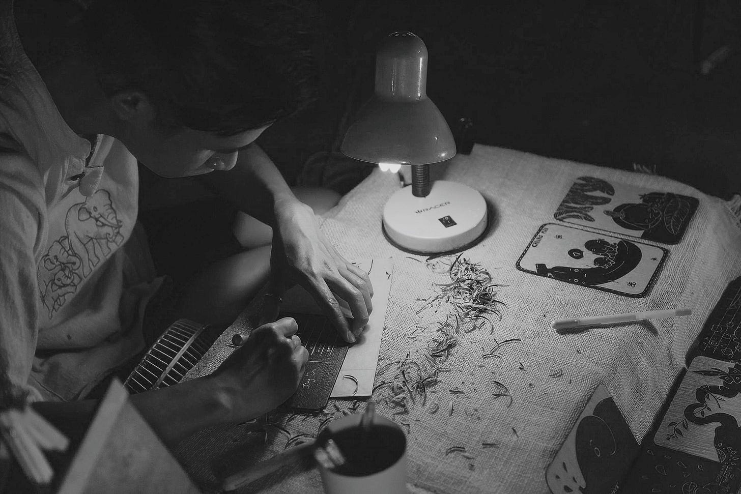 A man making Chinese crafts by table lamp for article about small business by Larry G. Maguire