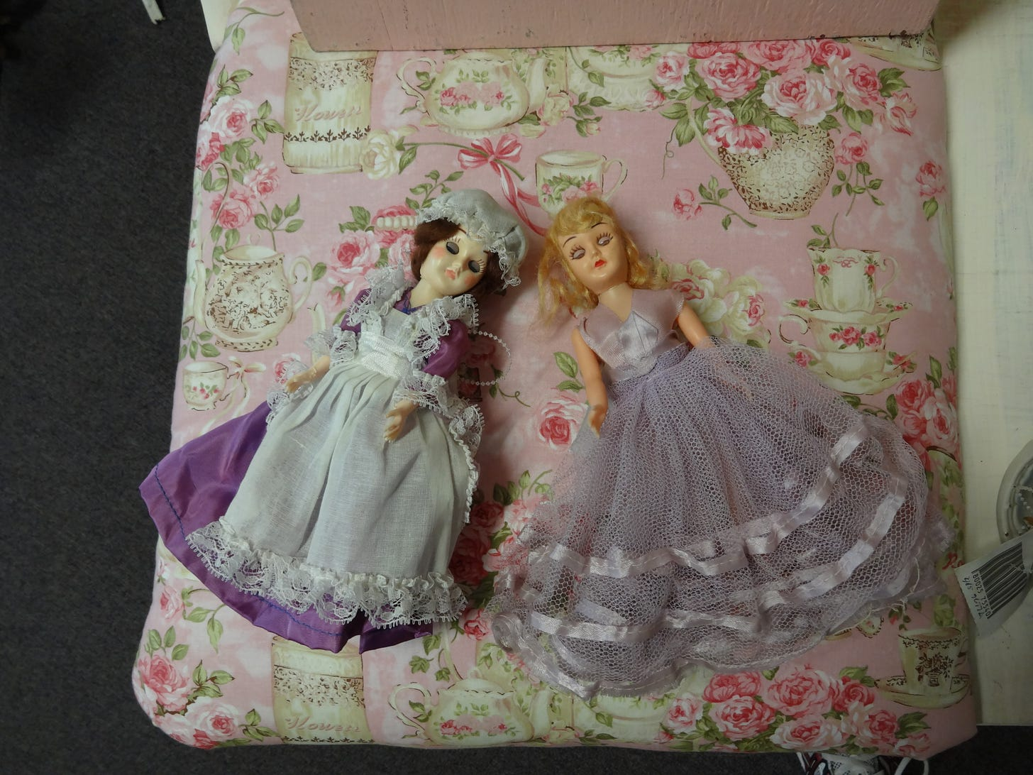 Two antique dolls lying on a chair