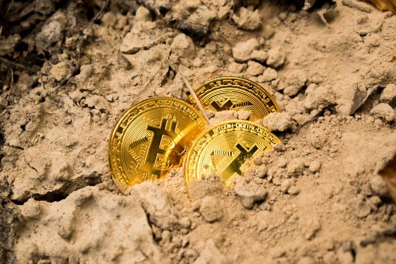 Three golden bitcoins buried in the sand.