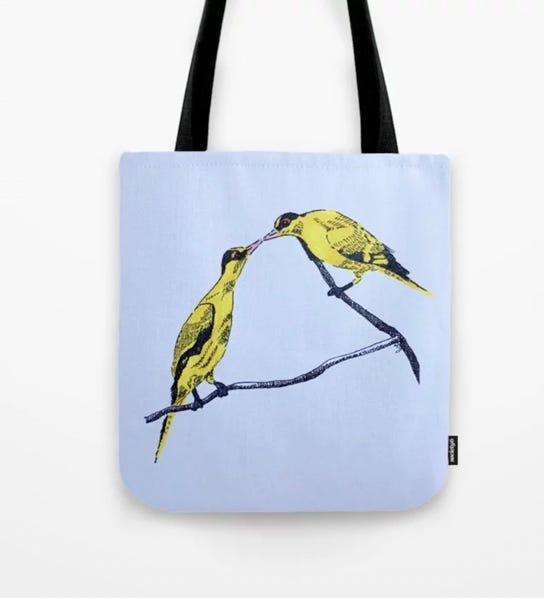 photo of Commitment art on a tote bag. Two bright yellow black-naked oriole birds perched on a branch, with their beaks touching, like kissing