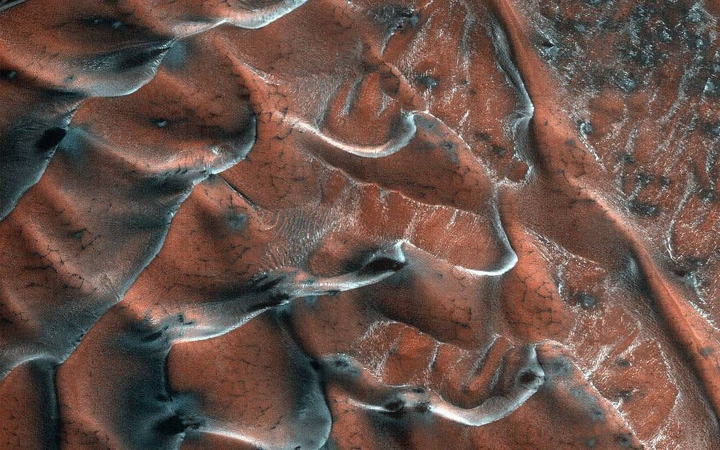 A field of sand dunes occupies this frosty 5-kilometer diameter crater in the high-latitudes of the northern plains of Mars.