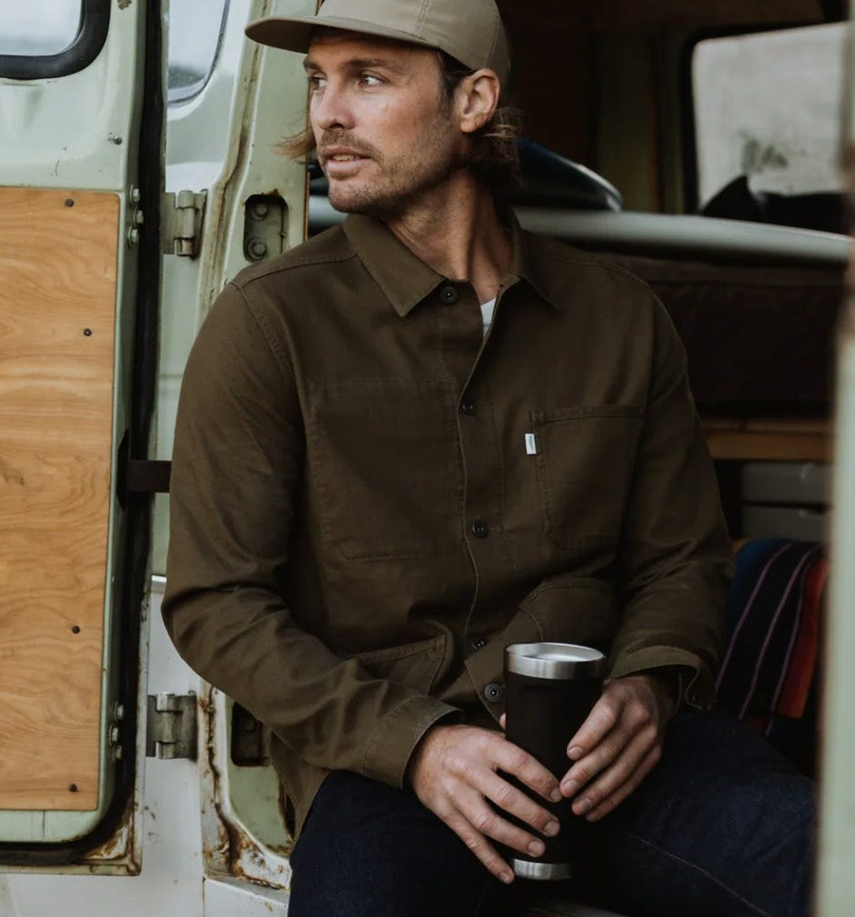 a man sitting in a van with a coffee cup wears the wellen stretch chore jacket