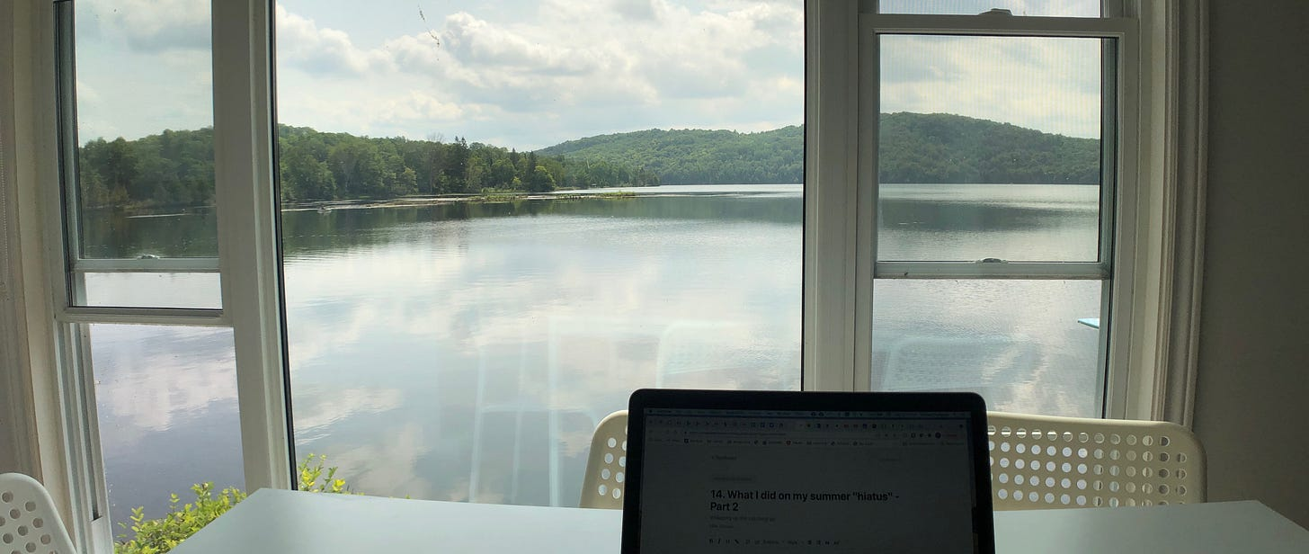 A computer on a table in front of a large window. Beyond the window is a wide view of a placid lake and green, rolling hills in the background.