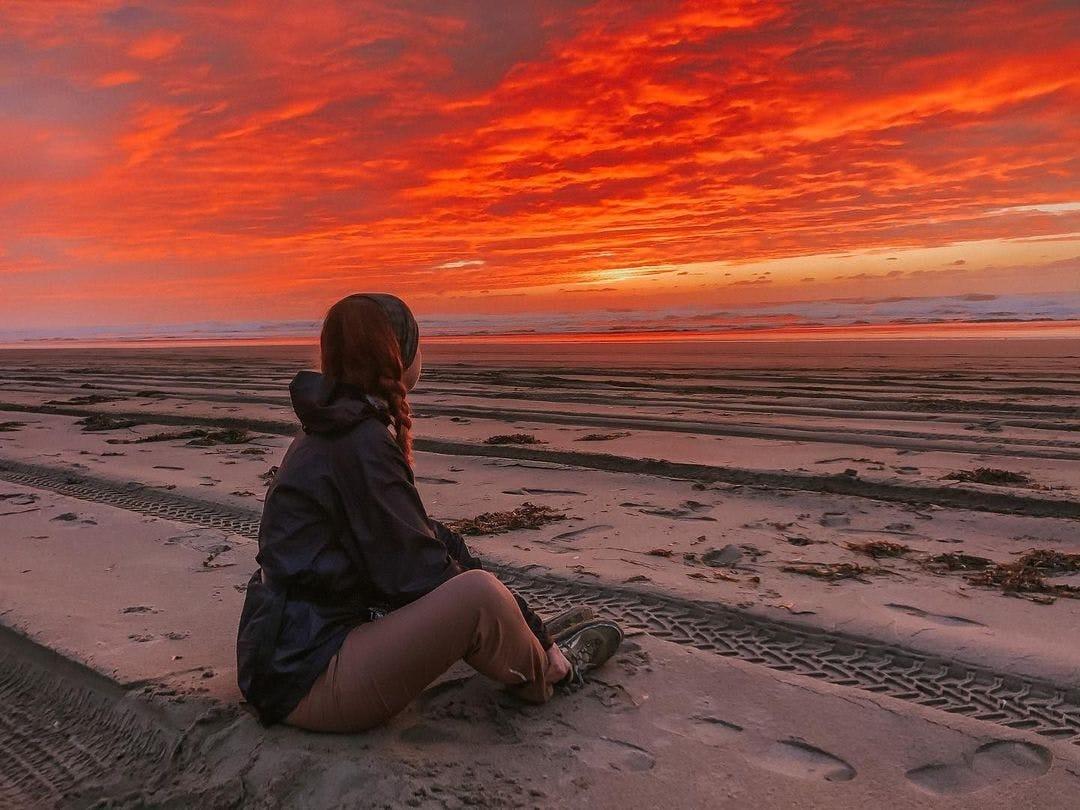 Red Sky women sitting on beach
