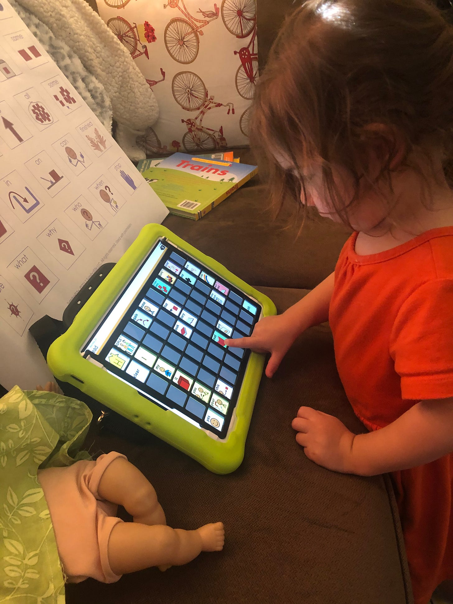 Photograph of Lila standing and pushing buttons on an AAC device.