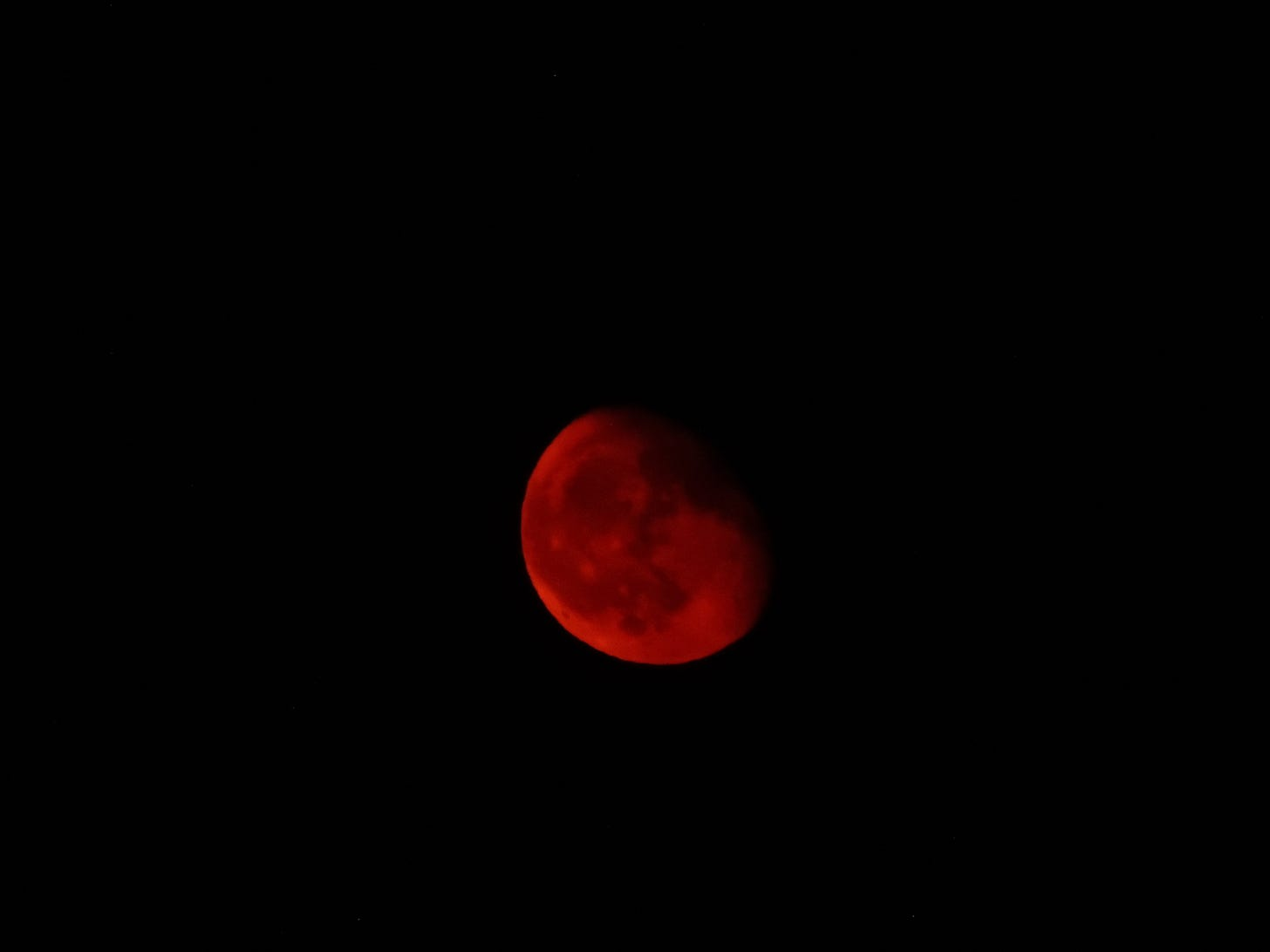 A blood red moon surrounded by black sky