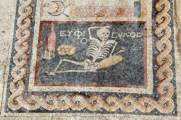 """Picture of an ancient Turkish skeleton mosiac that says """"be cheerful! Enjoy your life!"""""""