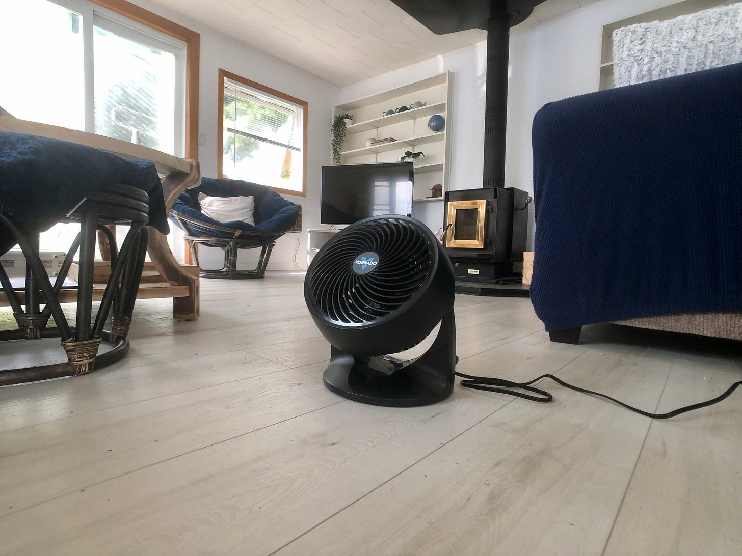 An electric fan on the floor of a cottage living room.