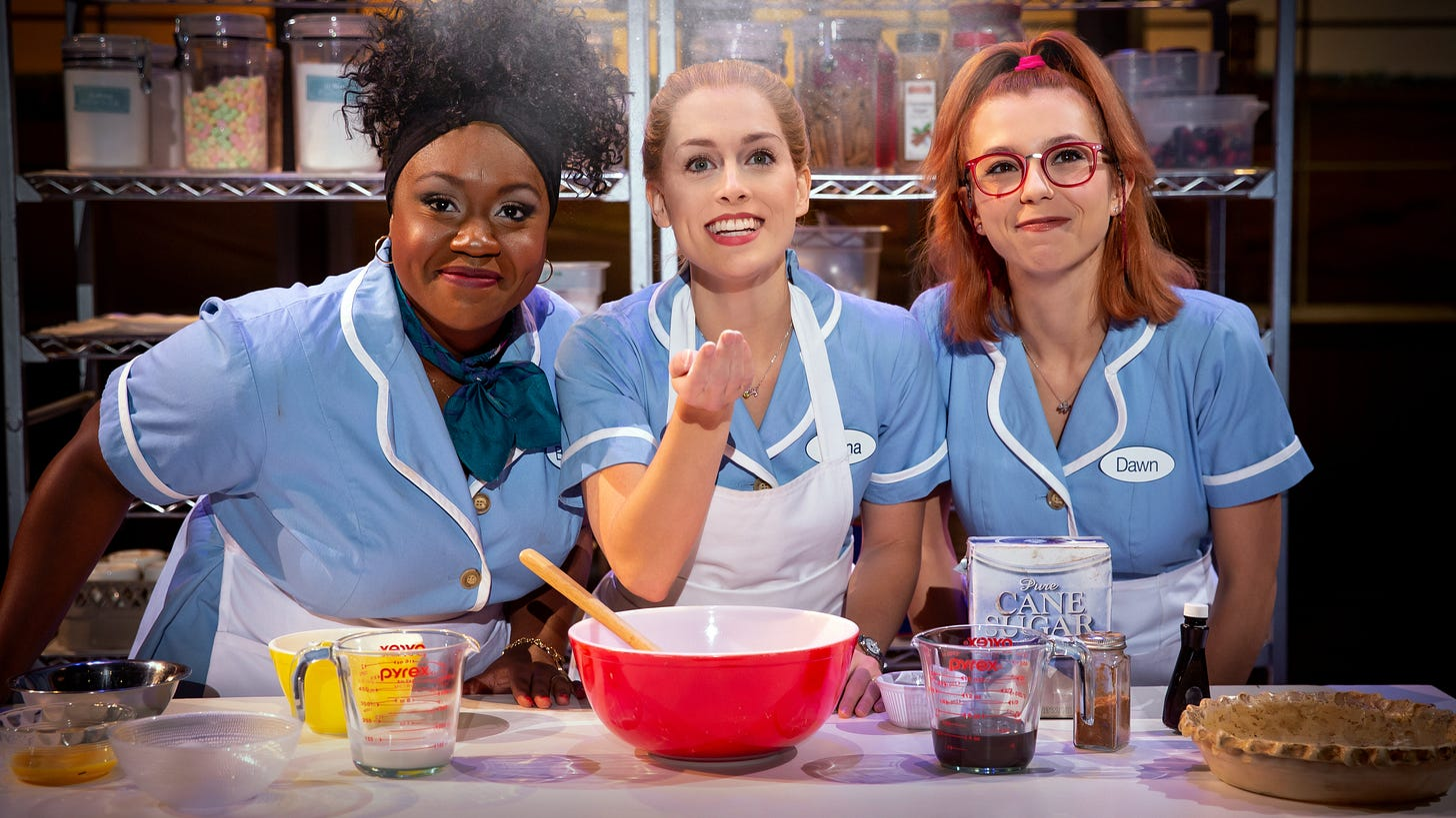 Kennedy Salters as Becky, Bailey McCall as Jenna, and Gabriella Marzetta as Dawn lean over a mixing bowl on a kitchen counter top dressed in waitress uniforms.