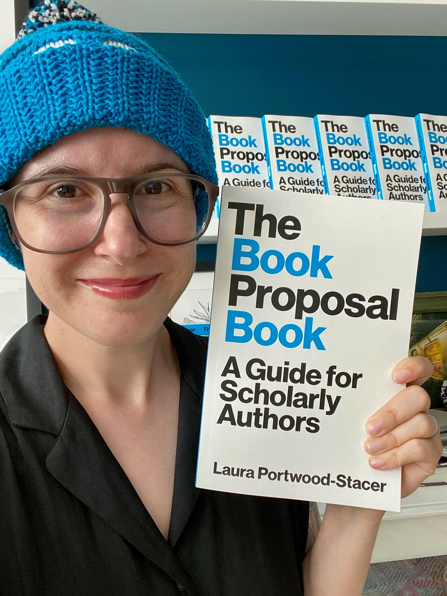 A photo of me holding up The Book Proposal Book and wearing a knitted cap in colors that match the book's cover (bright blue, white, and black)