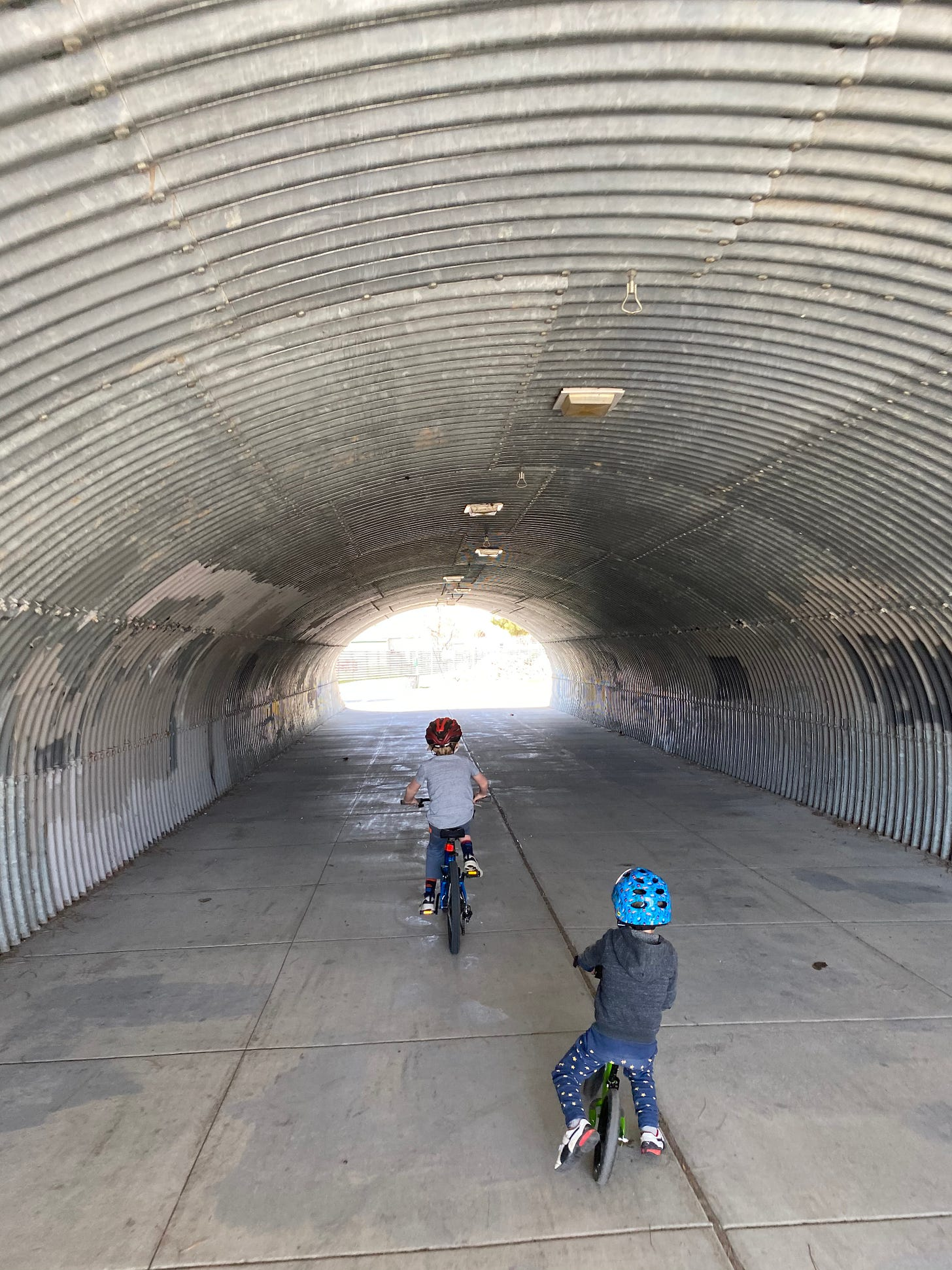 My two kids (one smaller than the other), riding their bikes through a corrugated metal tunnel, towards the sunlight