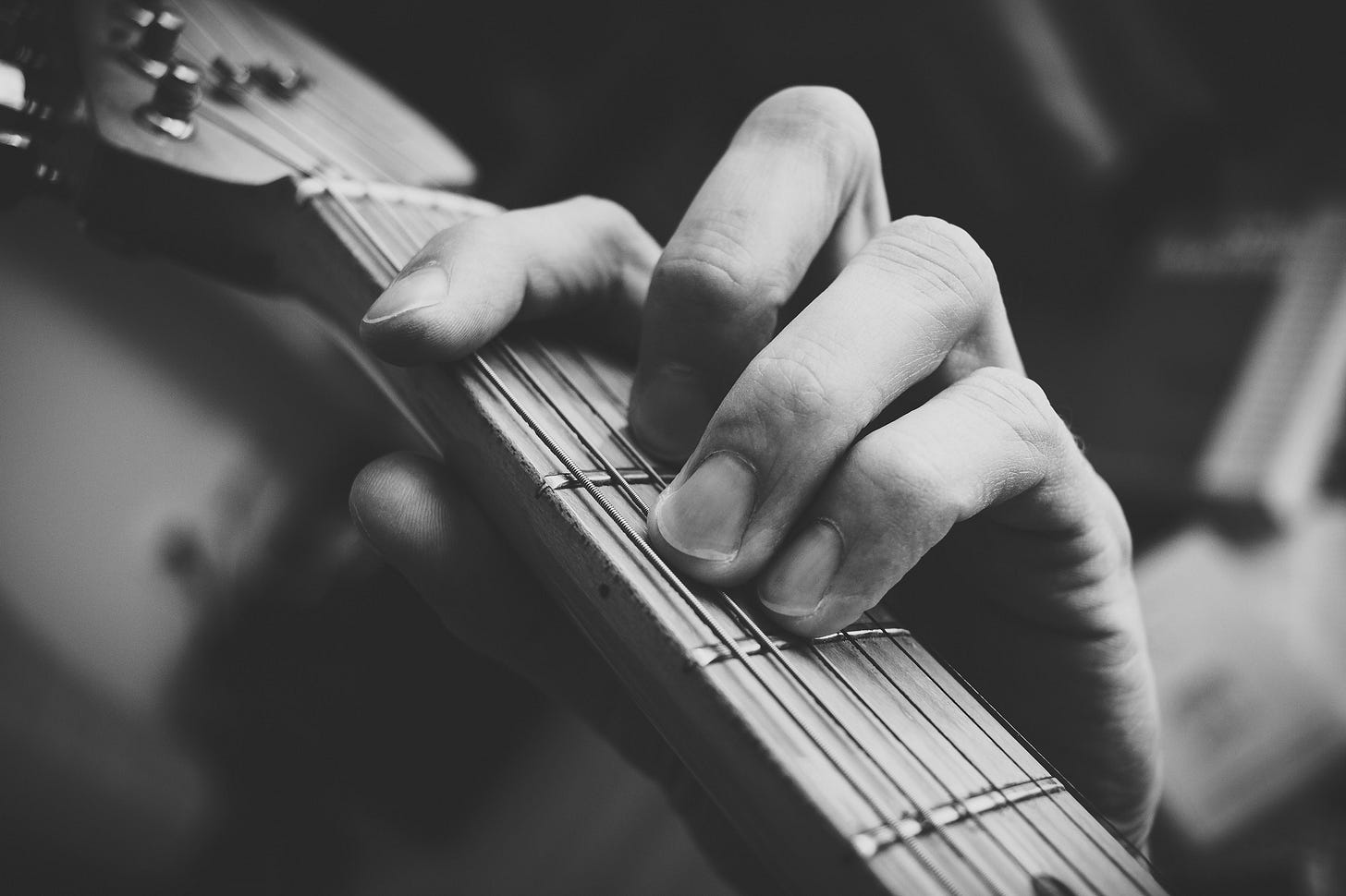 """Image of a man practising guitar for article titled """"Practice Intensely, Show up, Then See What Happens"""" by Larry G. Maguire"""
