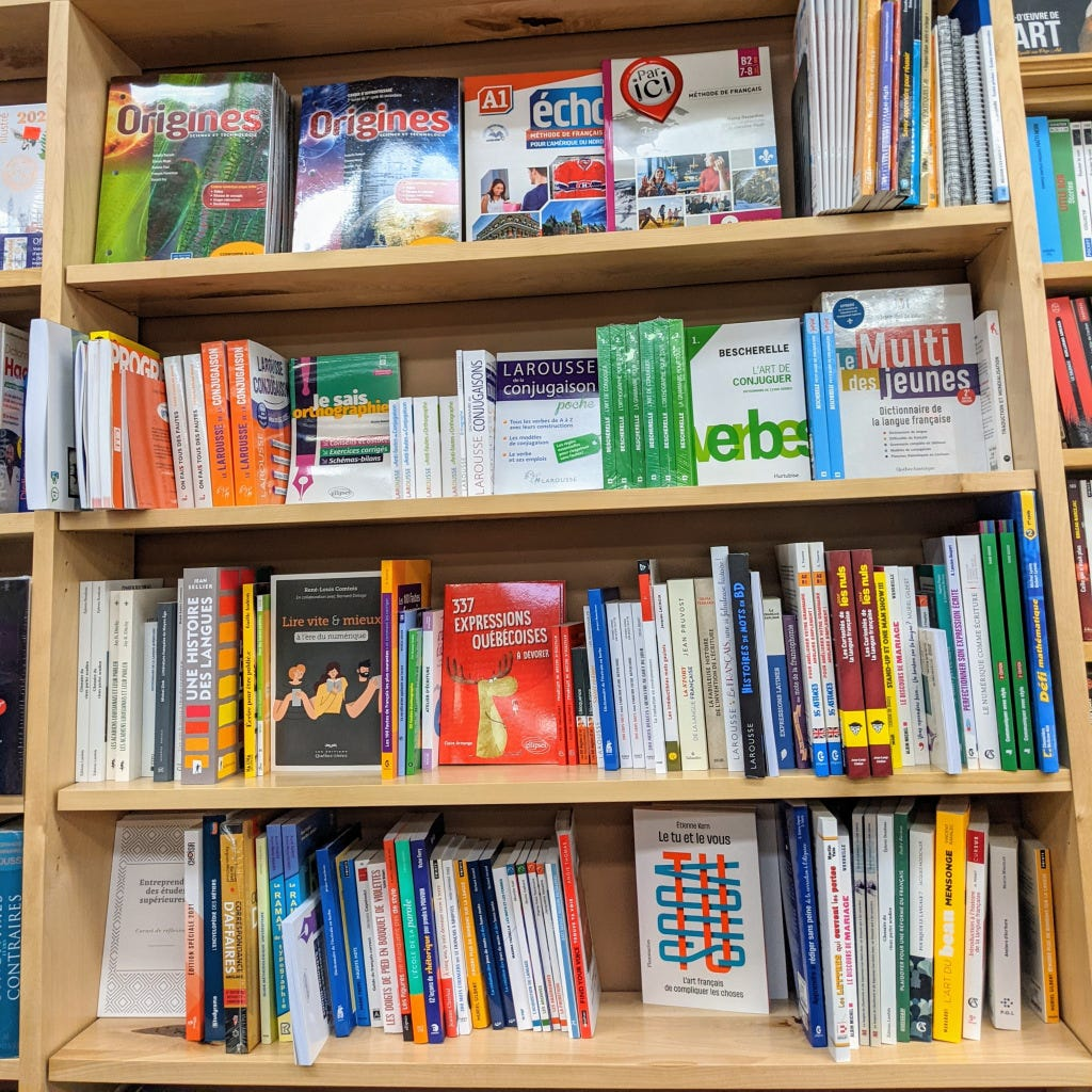 A bookshelf containing linguistics and reference books in French, including 337 Expressions Quebecoises, Le tu et le vous, and Une Histoire des Languages.
