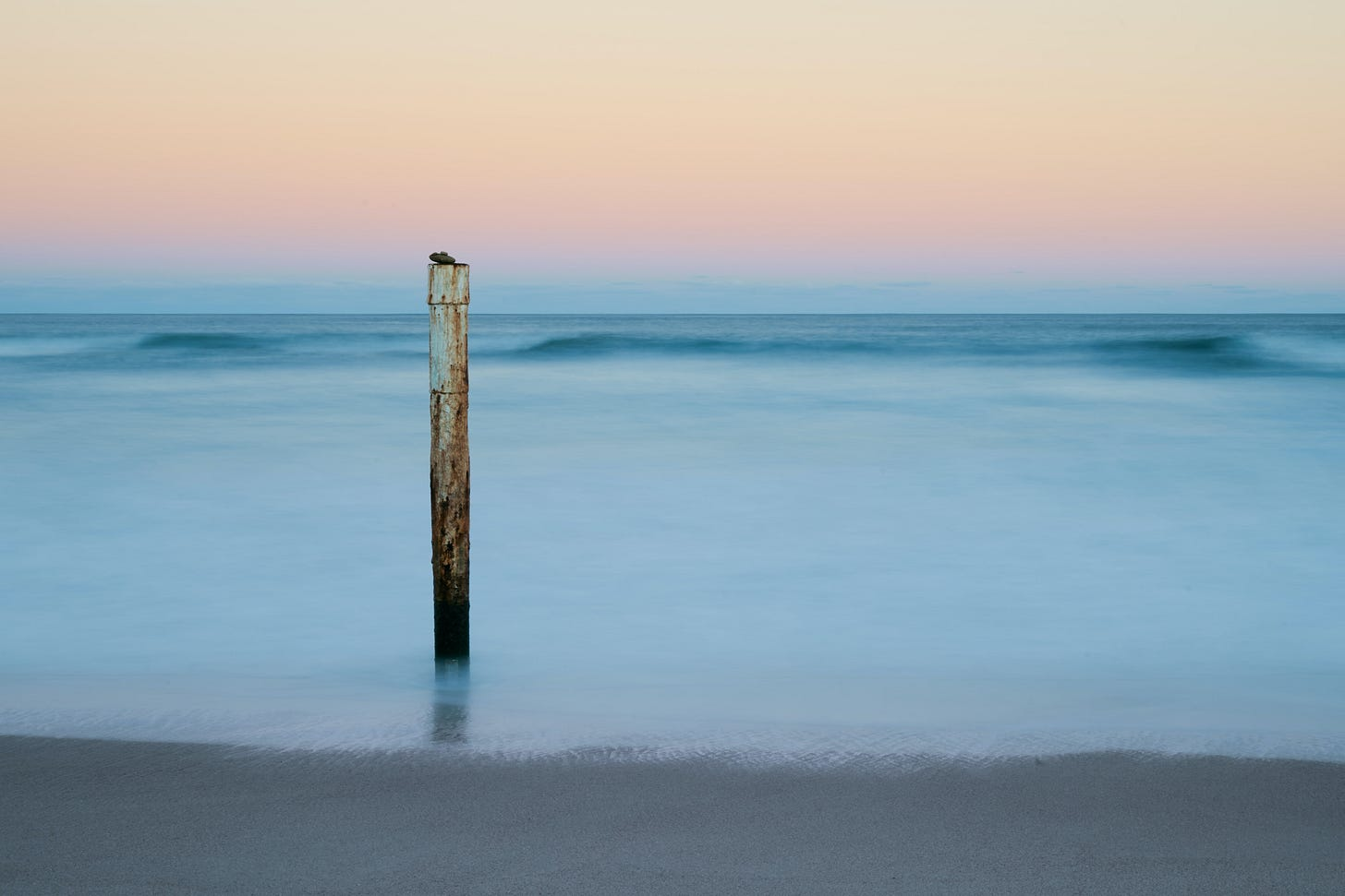pole sticking out of the sand and water on a beach