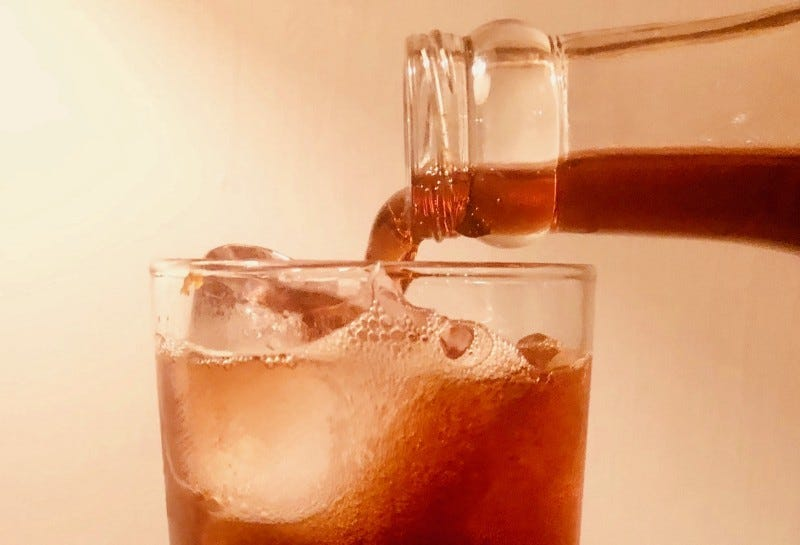 Closeup of a reddish-brownish liquid being poured from a clear bottle into an almost-full glass with ice in it.
