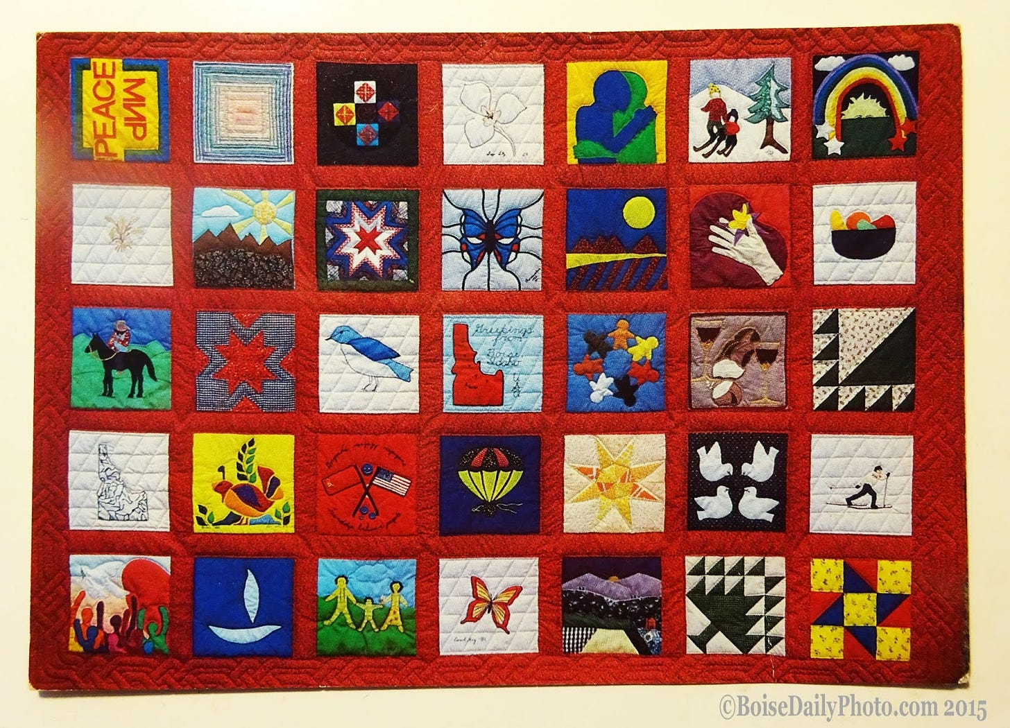 """A vintage postcard (1982) featuring the first Boise Peace Quilt. This was a Cold War quilt. From the back of the card, """"A gesture of friendship to the ordinary people of the Soviet Union from 25 Idahoans."""" The Boise Peace Quilt project still makes quilts today.    Postcard photo credit: Lenoard Nolt"""