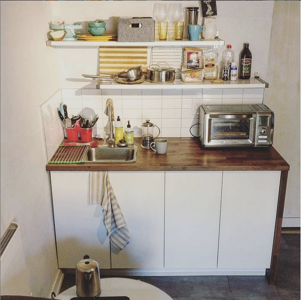 A counter top the width of two cabinets with two shelves above. There's a tiny bar sink, a toaster oven, a kettle, and a hot plate. There are two shelves above holding dishes, pans, and food. The cabinets hold a mini fridge and the water heater.