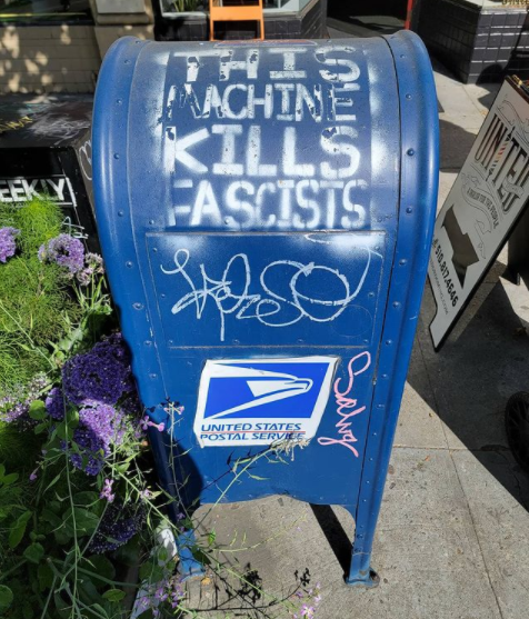 """Photo of a blue mail box that has words stenciled in white that say, """"this machine kills fascists"""""""