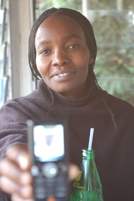 black woman with long braids holding a cell phone toward the camera