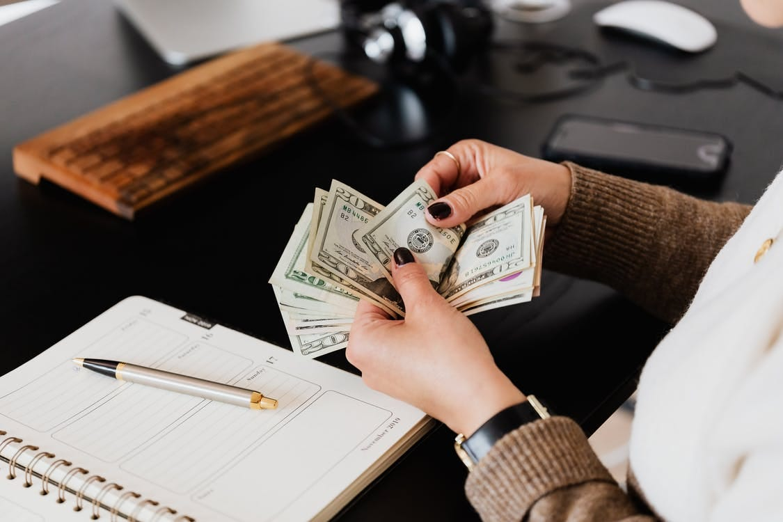 Unrecognizable elegant female in sweater counting dollar bills while sitting at wooden table with planner and pen