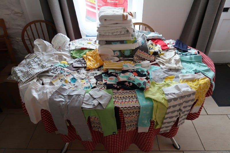 The contents of a Finnish baby box; dozens of items of clothing and accessories.