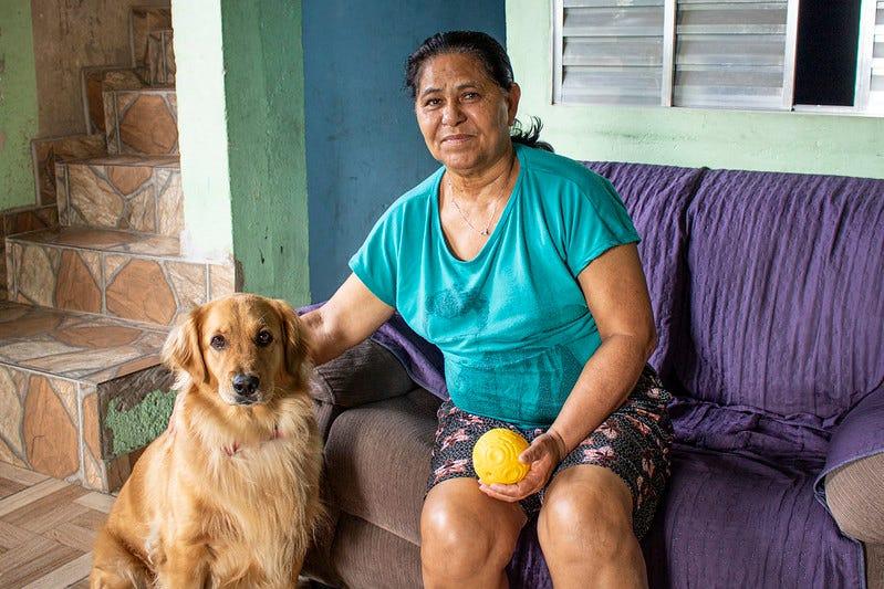 Maria ao lado de Meg, a cadela labrador que era da filha caçula. Ela veio do Alagoas para visitar o marido e nunca mais voltou | Ira Romão/Agência Mural