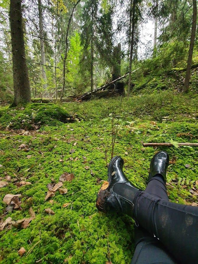 um par de pernas e botas pretas sujas de terra, cruzadas, no chão da floresta. árvores ao fundo