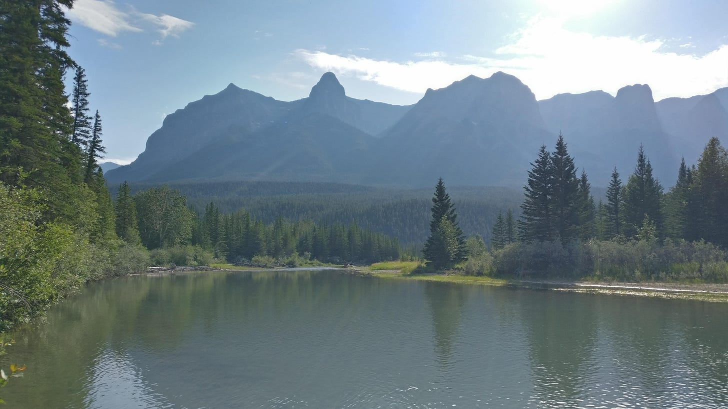 A picture of Canmore, taken from the side of a river with mountains visible in the hazy distance