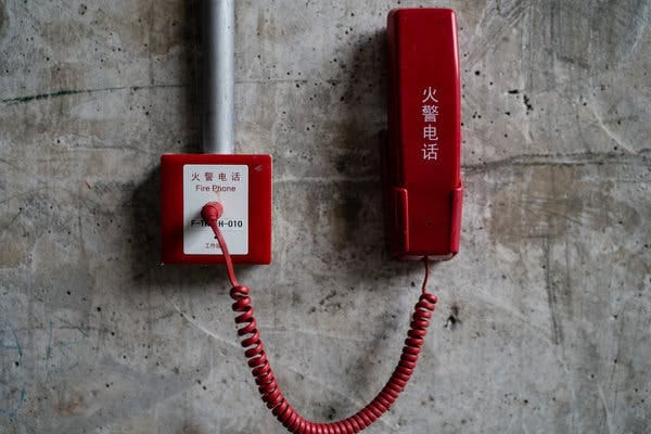 An emergency phone's markings make clear who built the dam.