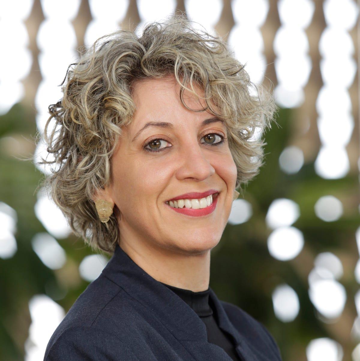 Foto de mulher loira com cabelo curto olhando para a câmera.