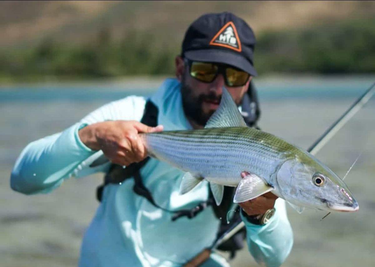 man holding a bonefish in hawaii