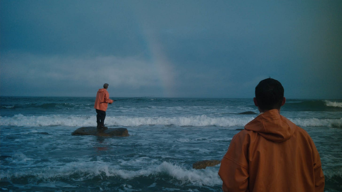An official still from the film 'Somewhere with No Bridges', where two fishermen stand off a beach, fishing into the ocean during the day, with a rainbow in front of them in the distance.