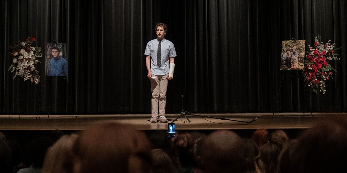 Ben Platt as Evan Hansen stands alone on an auditorium stage at a memorial for a fellow student, as other students film him with their cellphones.