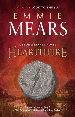 """Cover of the book """"Hearthfire"""" by Emmie Mears. The cover features the title, author, the phrases """"Author of Look To The Sun"""" and """"A Stonebreaker Novel,"""" and the blurb """"Masterful storytelling."""" by Ellie Ann, New York Times Bestselling Author. The cover art is an illustration of a small gray stone with a lightning bolt carved into it, pictured against a blurry wetland landscape with a red-tinged sky."""