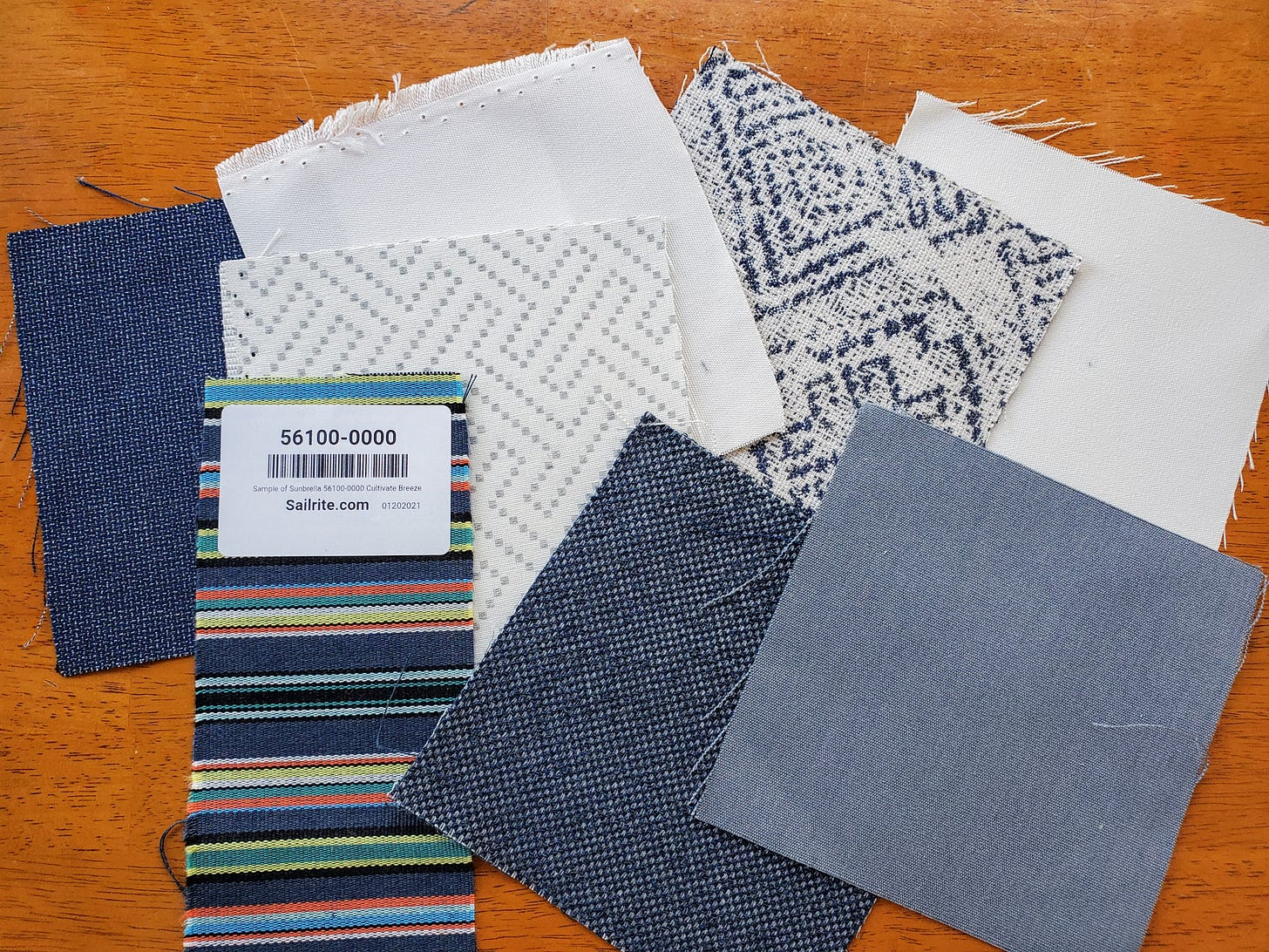 Image: square samples of Sunbrella fabric in blues and whites on a wood table top.