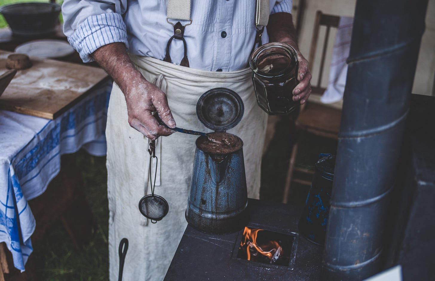 Craftsman making coffee on an old stove for article by Larry G. Maguire