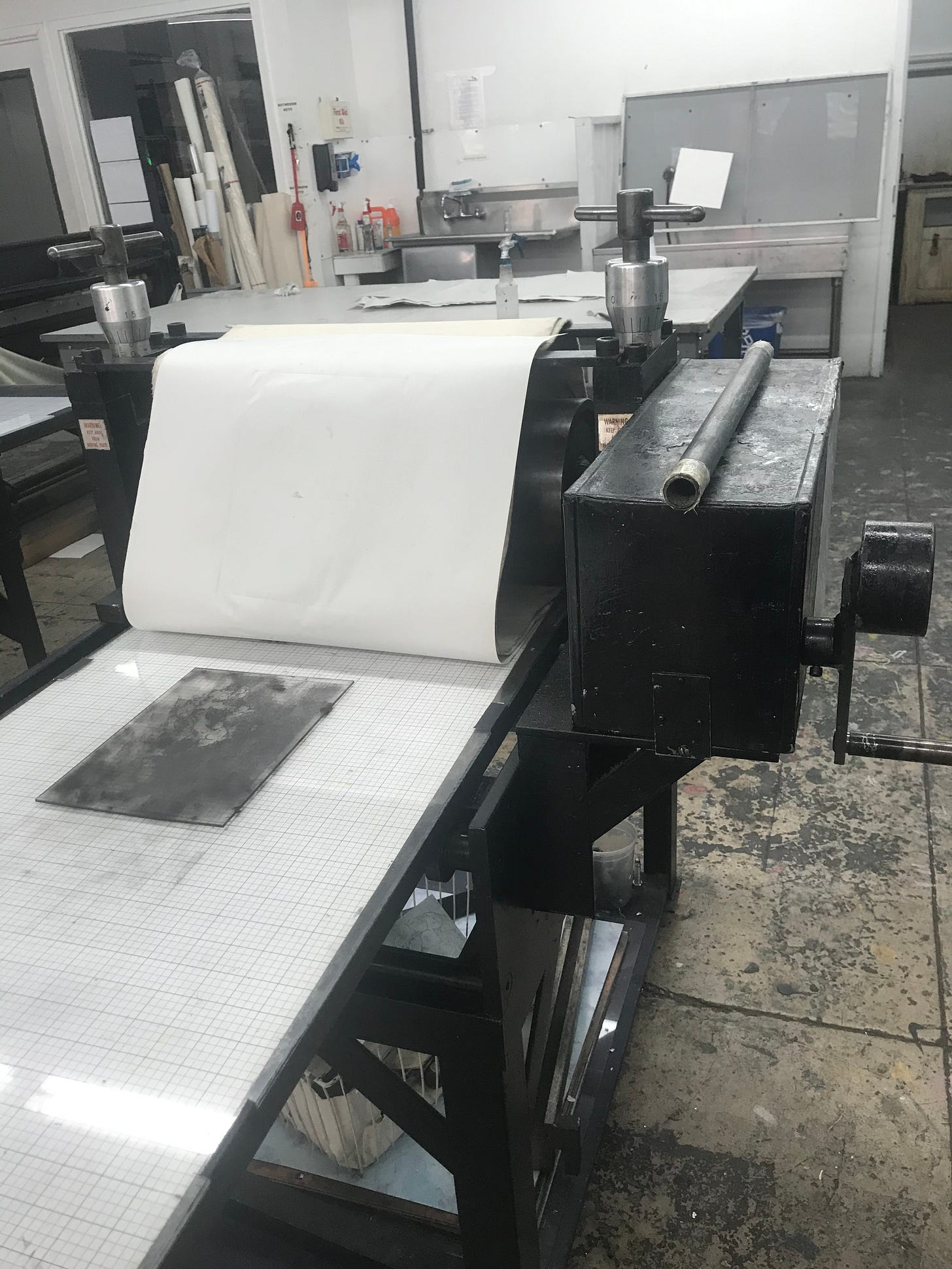 Documentation of intaglio process.  The image shows a large etching prress with an inked plate.