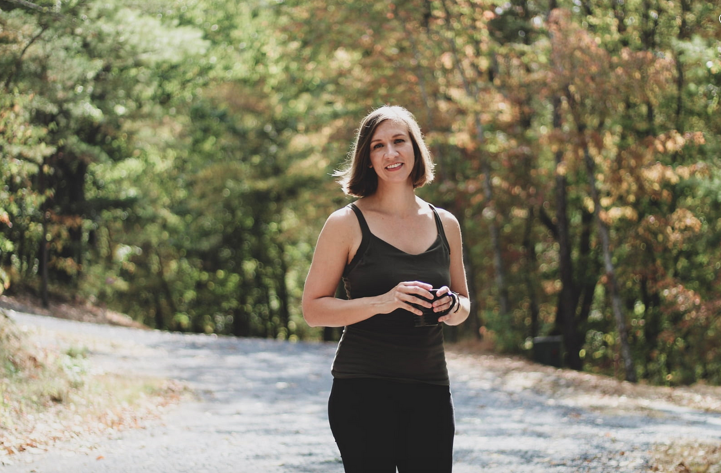 A white, brunette woman in an olive tank top and black pants holds a black coffee mug on a trail in the woods