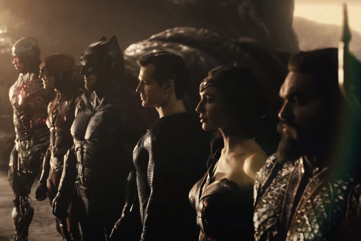 From 'Zack Snyder's Justice League, right to left: Aquaman, WonderWoman, Superman, Batman, The Flash, and Cyborg. They stand united, looking off into the distance, after a victory.