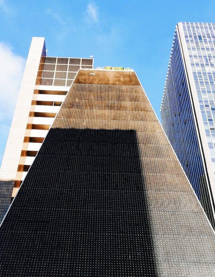 Foto mostra prédio preto em formato triangular em contraste com céu azul.