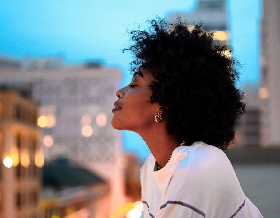 Confident young woman gazing at city lights from above