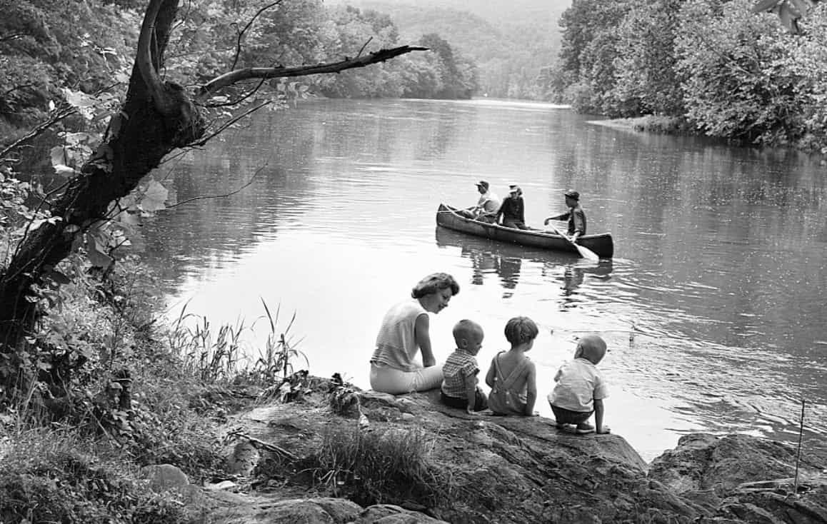 woman with children sitting on rocks by river