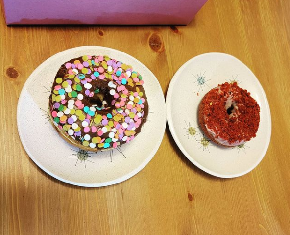 photo of two donuts, each on a small vintage dessert plate. One donut has chocolate frosting and round confetti rainbow sprinkles, the other is a red velvet donut with a red crumbly topping